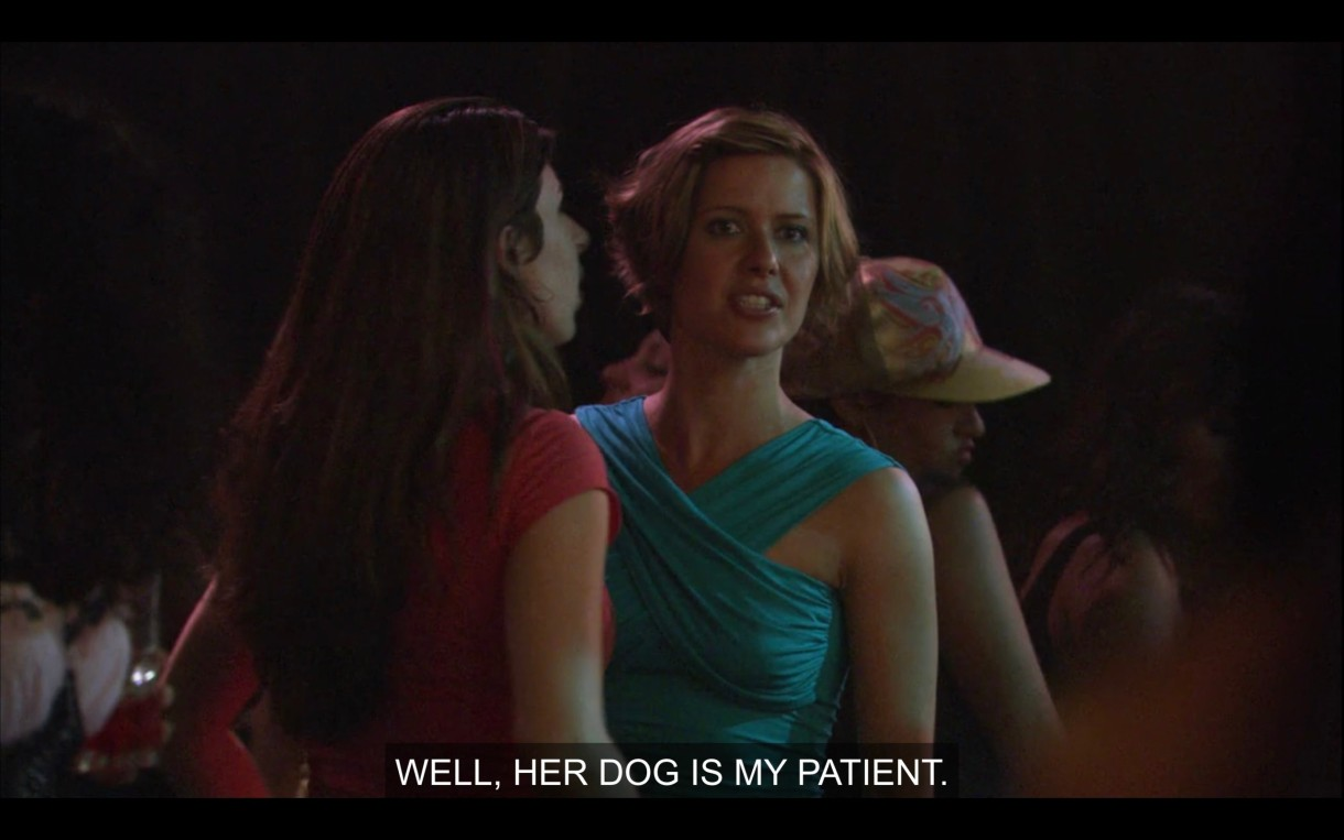 """Jenny's vet with short blonde hair and wearing a light blue dress, says, """"Well, her dog is my patient."""""""