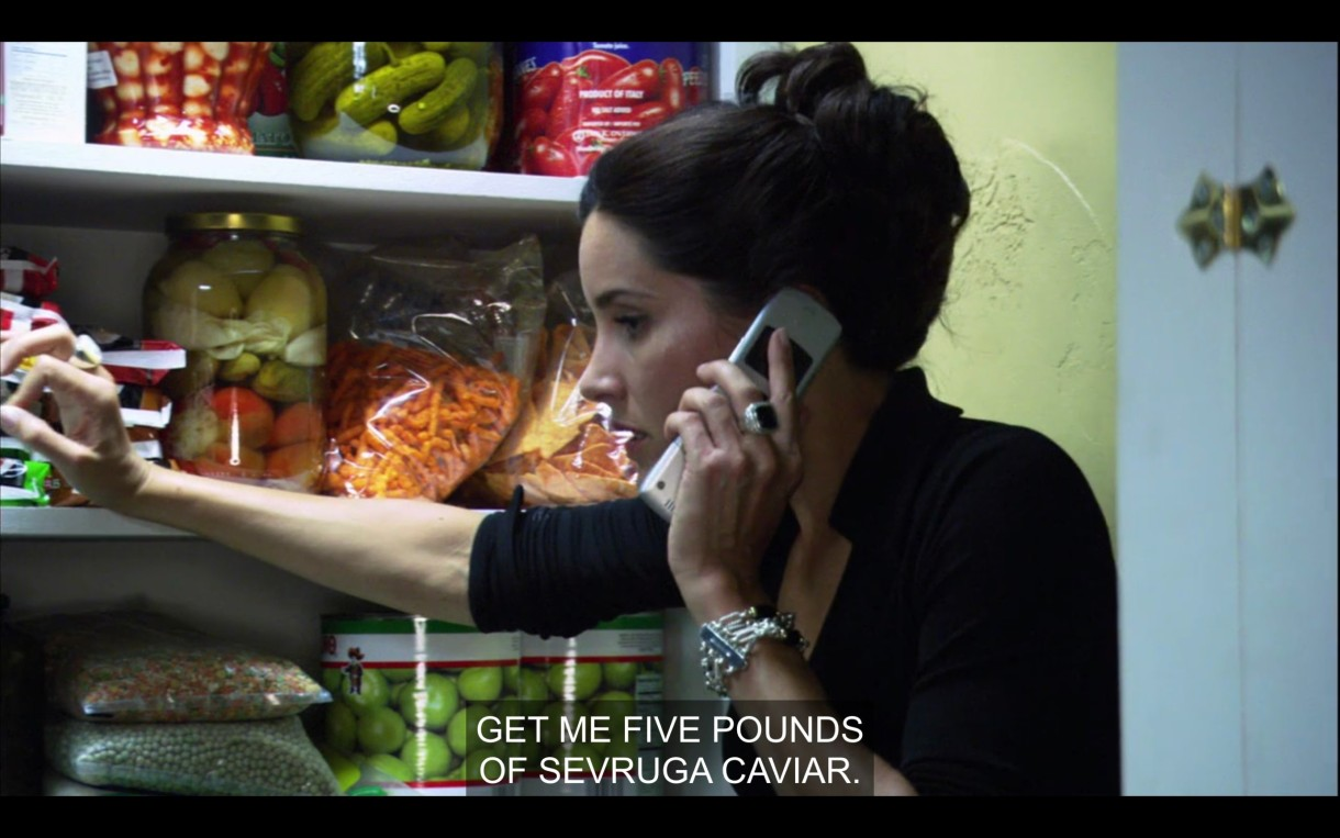 """Helena standing in a walk-in holding a cell phone to her ear. She looks stressed. She says into the phone, """"Get me five pounds of sevruga caviar."""""""