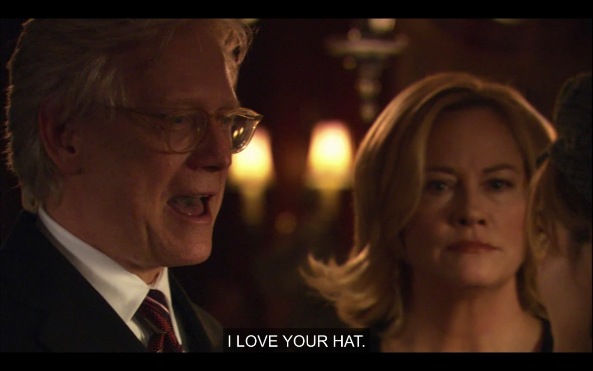 """An old white guy with glasses and a suit stands next to Phyllis in a dimly lit room. """"I love your hat."""""""