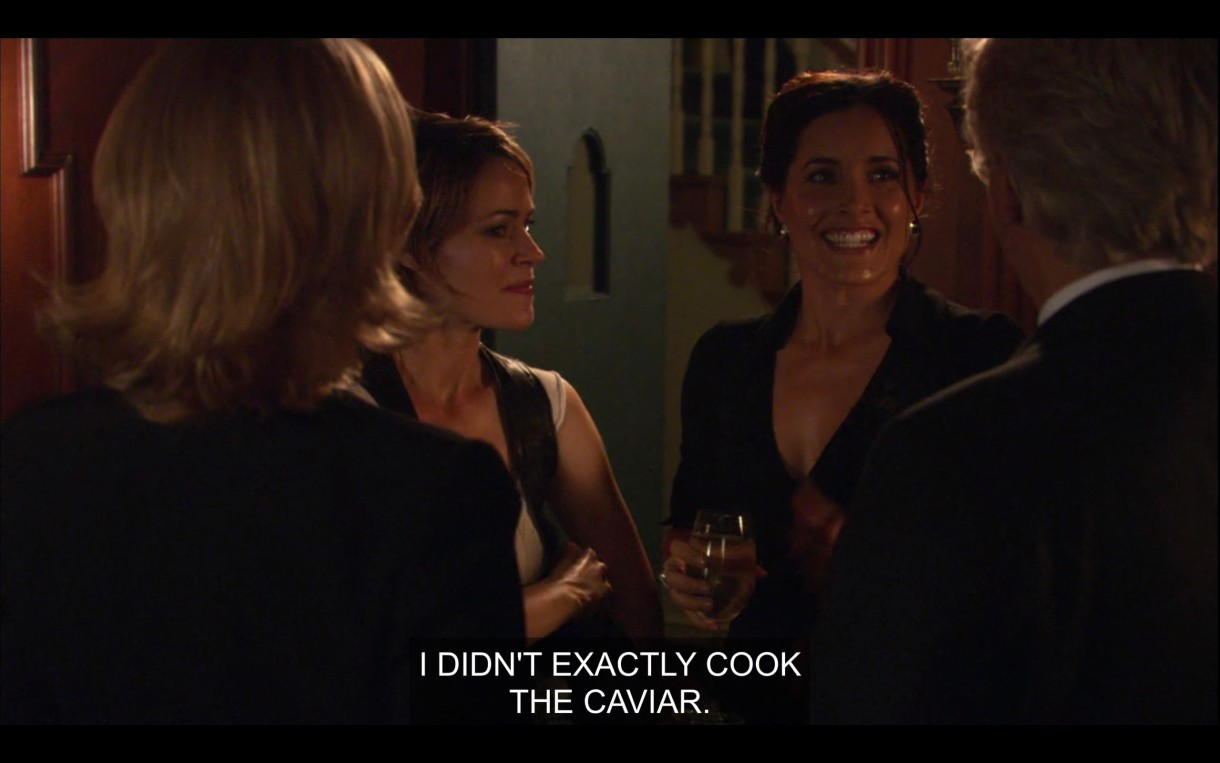 """Alice Helena stand across from Phyllis and her husband. Helena says, """"I didn't exactly cook the caviar."""""""