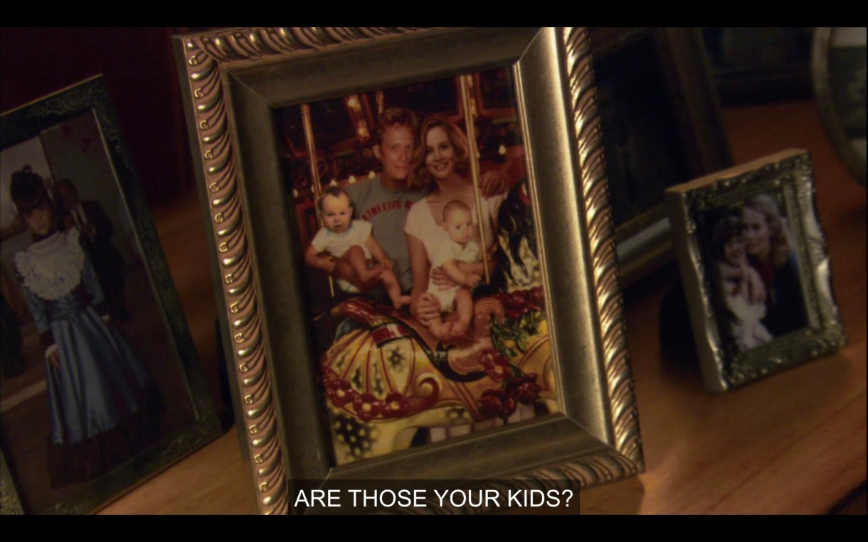 """Framed photo of a white couple with two babies on a carousel. """"Are those your kids?"""""""
