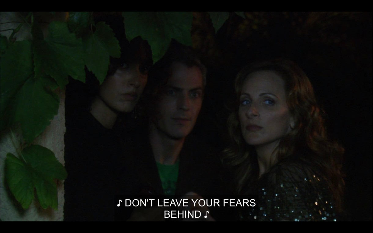 """Bette, Tom, and Jodi stand together outside in the dark. Music is playing, singing, """"Don't leave your fears behind."""""""