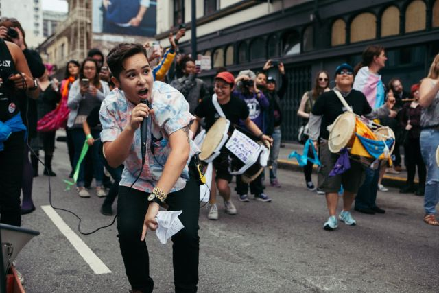 Sammie bends low to the ground to speak into a mic at a march while people behind them play drums