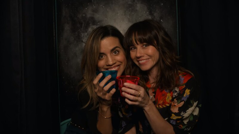 Image: Judy is in a photobooth with drinks and her girlfriend, played by Natalie Morales. They are smiling.