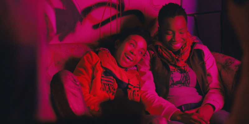 Two girls laughing in a red-lit room in Pariah