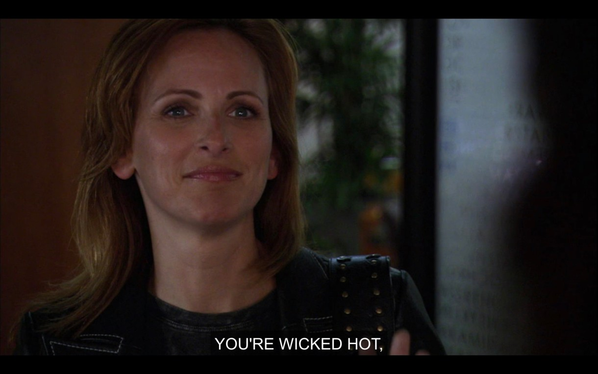 """Jodi, in a black blazer, stands in Bette's office. She's smiling with her mouth closed. """"You're wicked hot."""""""