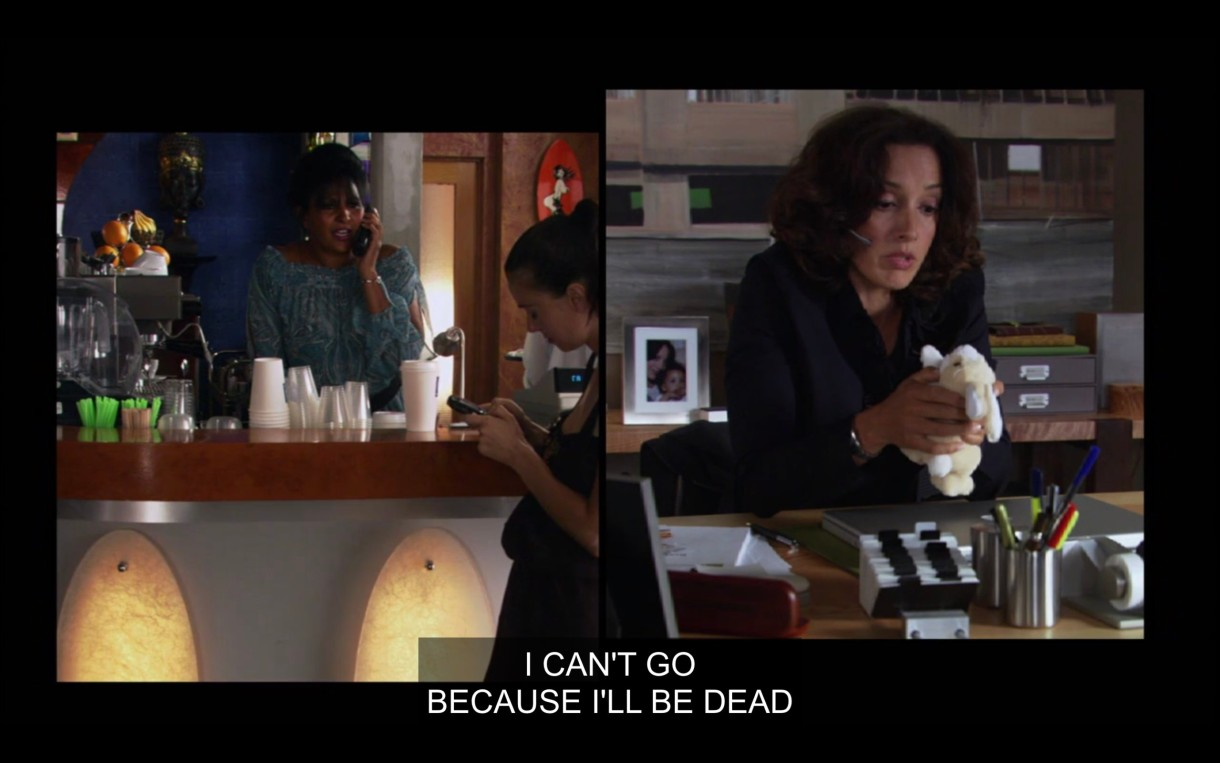 """Side-by-side visual of Kit and Bette talking on the phone. Kit is in a blue top standing behind the counter at The Planet. Bette is wearing a black blazer and is sitting at her desk, talking into a headset and holding a small white stuffed bunny. """"I can't go because I'll be dead."""""""