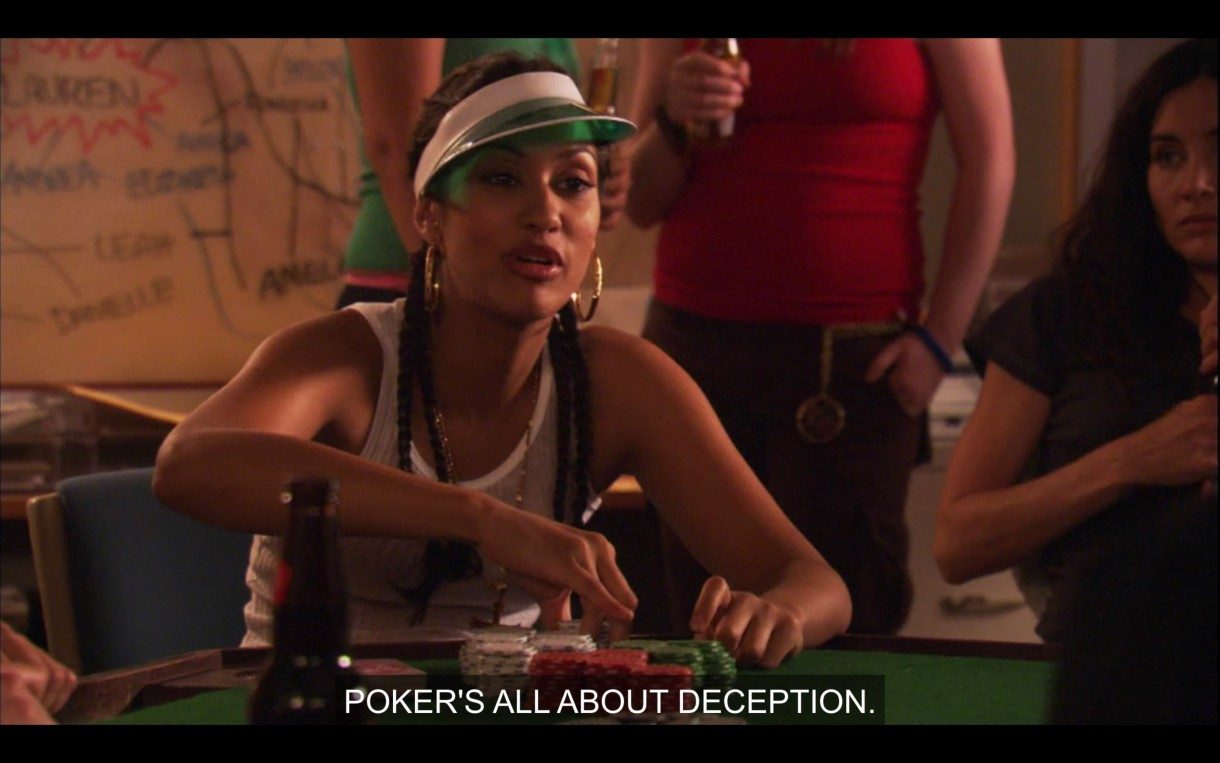 """Papi is in a white tank top and a green poker visor, sitting at a poker table with a stack of poker chips in front of her. She says, """"Poker's all about deception."""""""