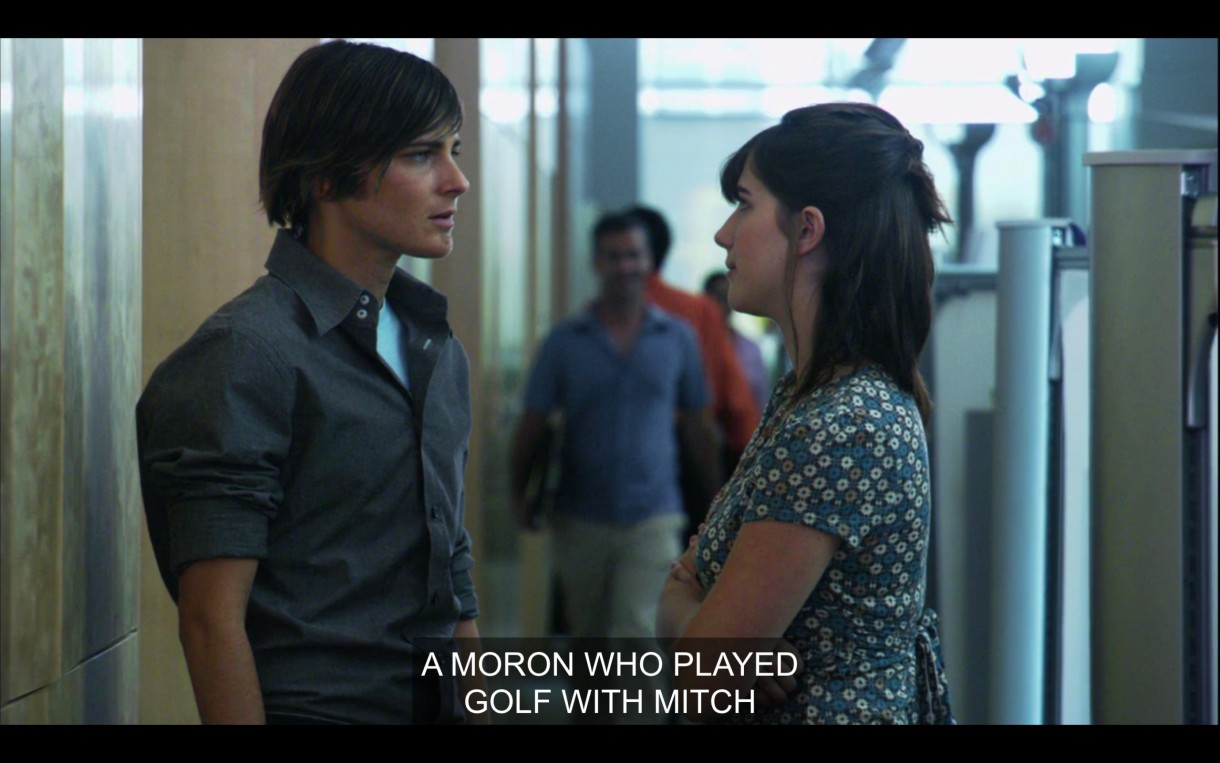 """Max (wearing a gray dress shirt) is standing in his work office facing a brunette women in a blue and green dress. """"A moron who played golf with Mitch."""""""
