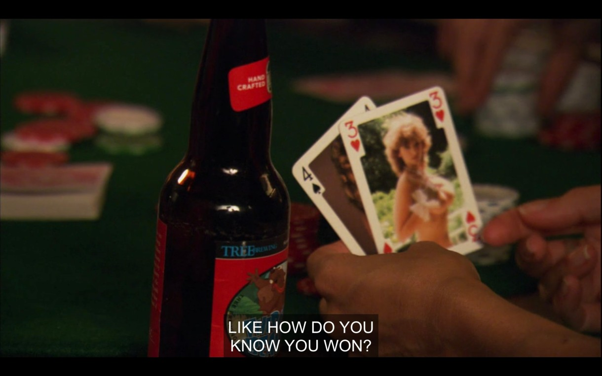 """A pair of hands holding 2 playing cards (a 4 of spades and a 3 of hearts) next to a beer bottle on a poker table. """"Like, how do you know you won?"""""""
