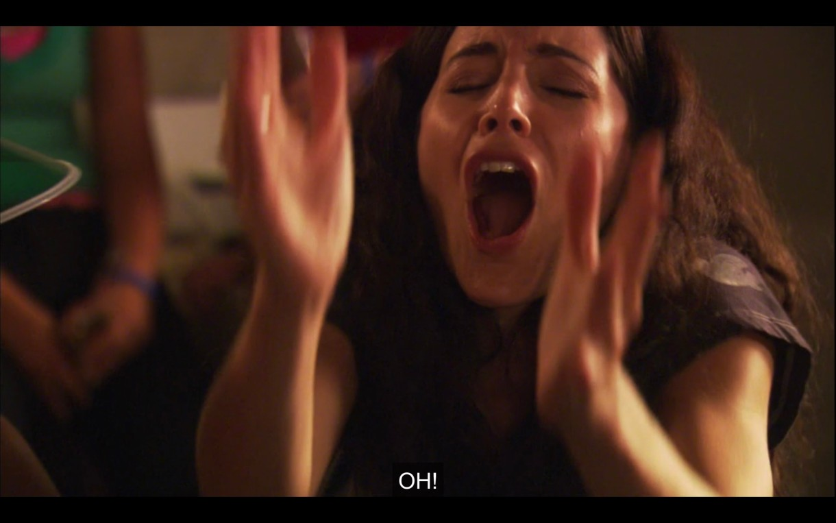 """Helena screaming """"Oh!"""" with her hands raised in the air, her mouth wide, her eyes closed."""