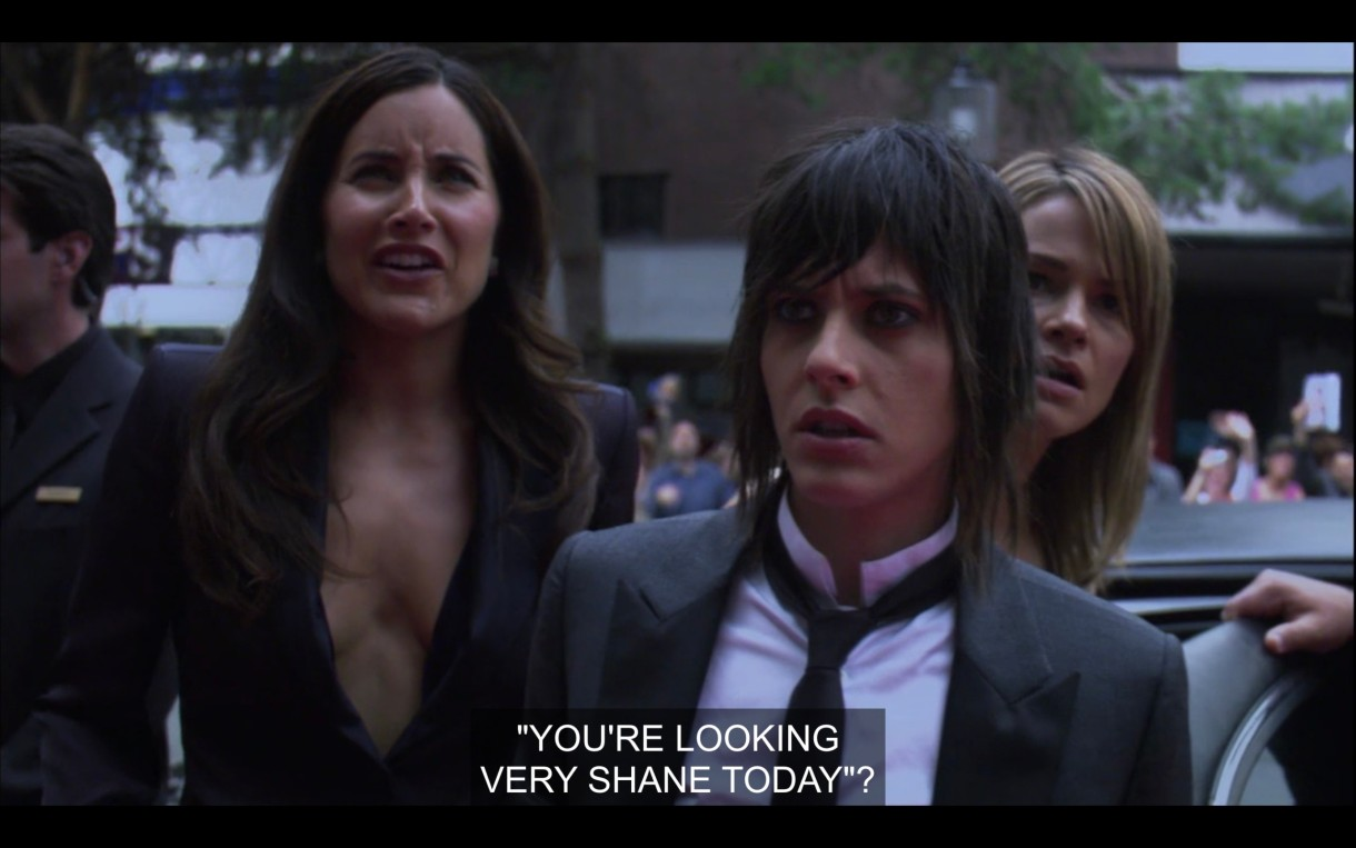 """Helena (wearing a high-cleavage black jacket), Shane (wearing a skinny black tie over a white shirt and a black blazer), and Alice (peaking over Shane's shoulder) first look at Shane's billboard. Helena reads, """"'You're looking very Shane today?'"""""""