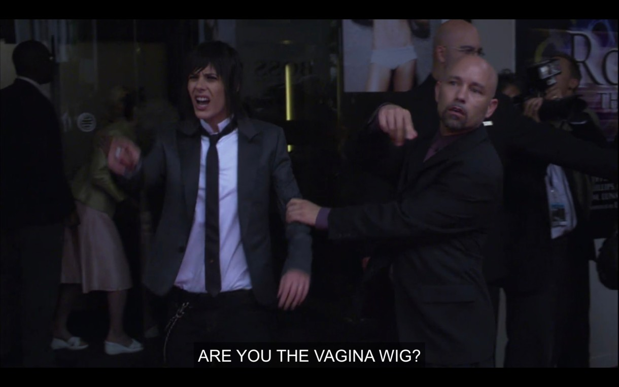 """Shane (wearing a black skinny tie, white shirt, and black blazer) is having her arm held back by a security guard in all black. She shouts, """"Are you the vagina wig?"""""""
