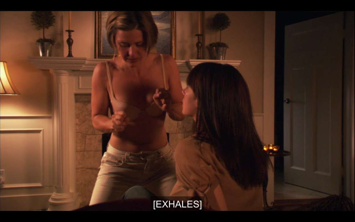 """Lindsey (wearing her bra and pants) straddles Jenny, who is sitting up on the couch. Subtitles read, """"[Exhales]"""""""