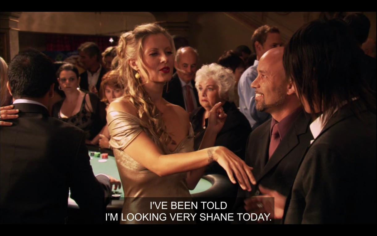 """Shane shakes the hand of a woman with long blonde hair and wearing a ball gown, standing in front of a poker table. She says to Shane, """"I've been told I'm looking very Shane today."""""""