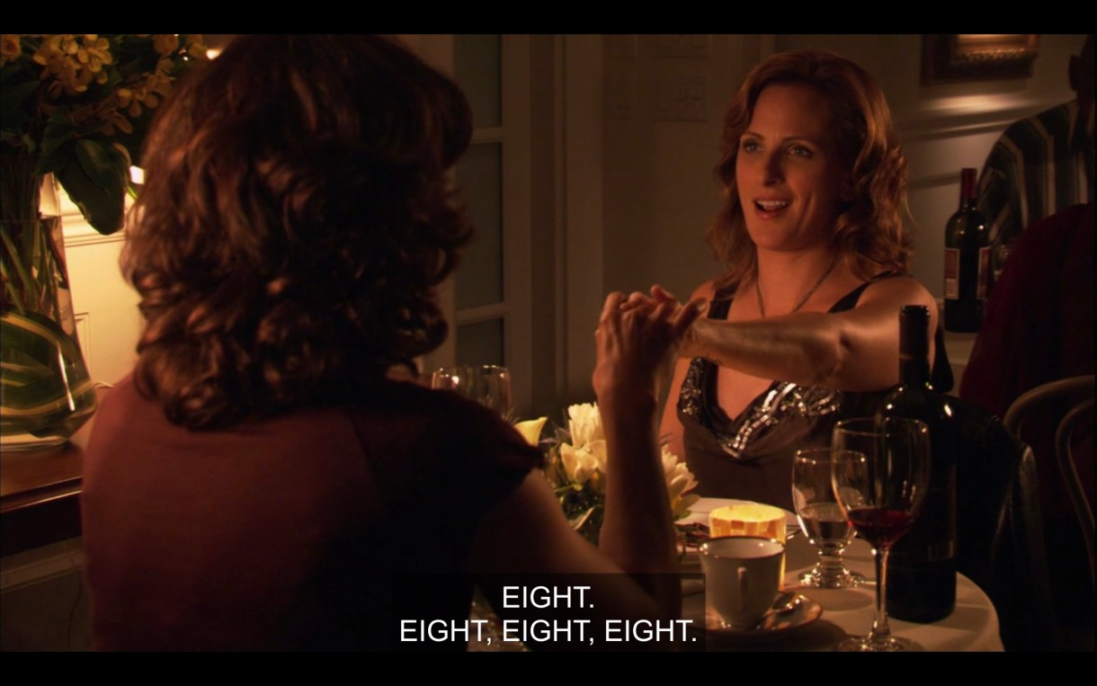 """Bette (wearing a brown top, her back to the camera) sits across a dinner table from Jodi. They're holding hands across the table. """"Eight. Eight, eight, eight."""""""