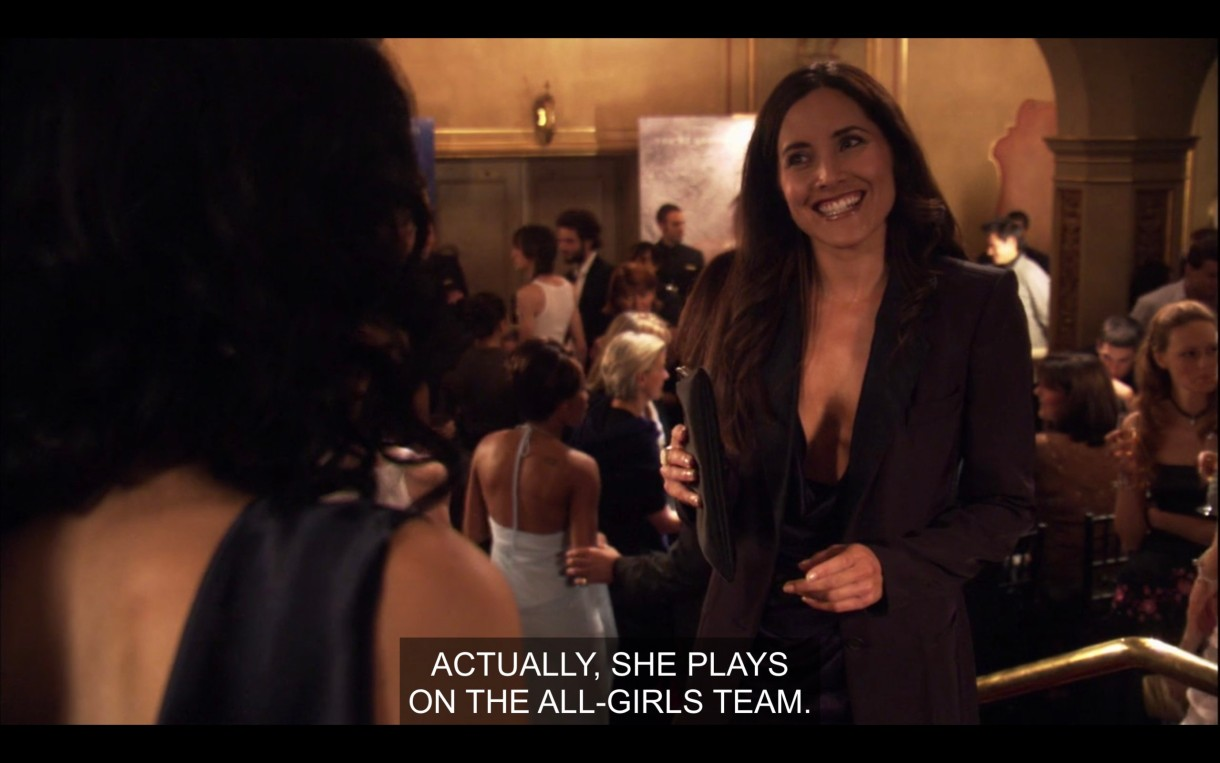 """Helena, wearing a high-cleavage black blazer and holding a black clutch purse is smiling in a crowded event hall. She says, """"Actually, she plays on the all-girls team."""""""