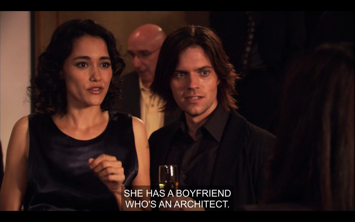 """A dark-haired man (wearing a suit and tie and holding a glass of wine) and dark-haired woman (wearing a black dress) look shocked and confused. """"She has a boyfriend who's an architect."""""""