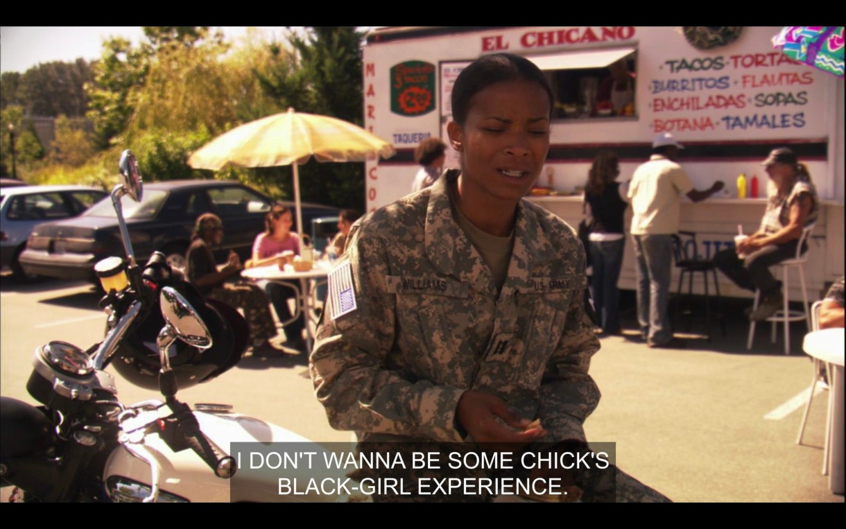 "Tasha in full military uniform. Her bike is parked behind her. We're outside, it's sunny. There's a taco truck in the background. Tasha is talking to Papi saying ""I don't want to be some chick's Black Girl Experience."""