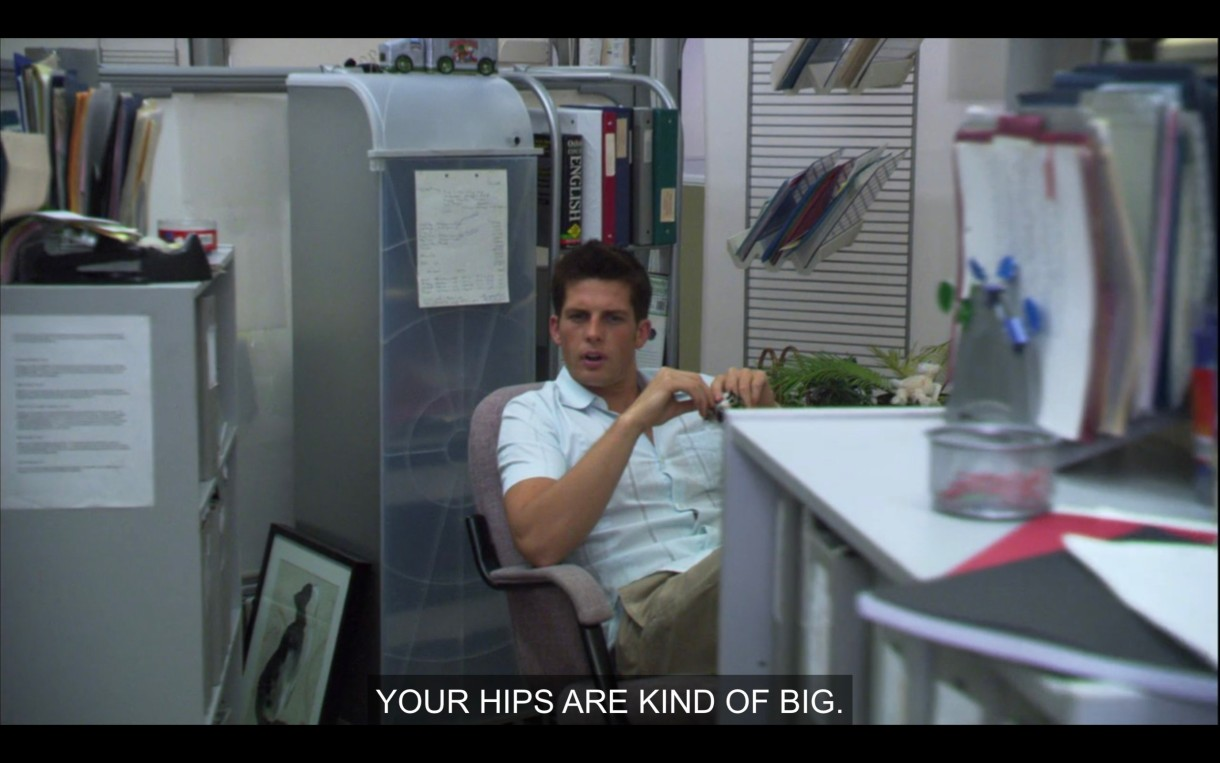 "In a boring office, a dude is leaning out of his cubicle to say ""Your hips are kind of big."""