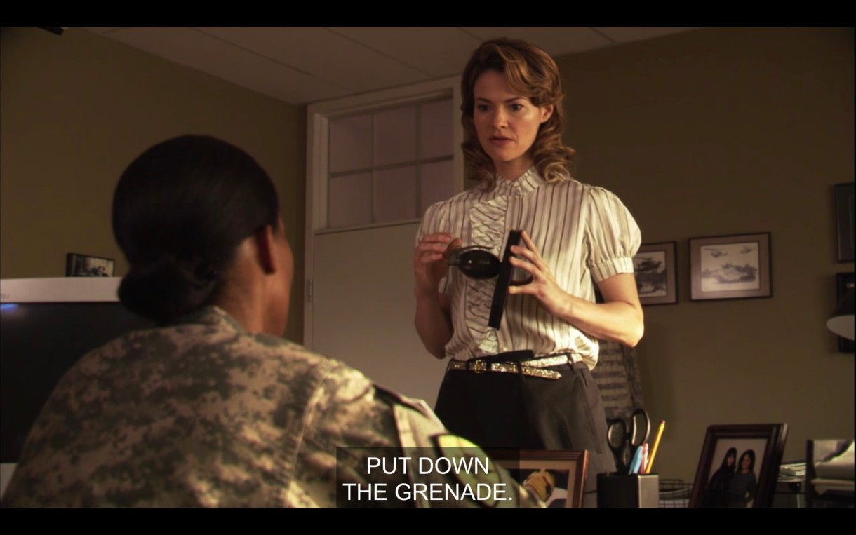 "In Tasha's office, Alice is standing in front of Tasha'a desk holding a grenade. Alice's hair is very 50s. The caption reads ""put down the grenade."""