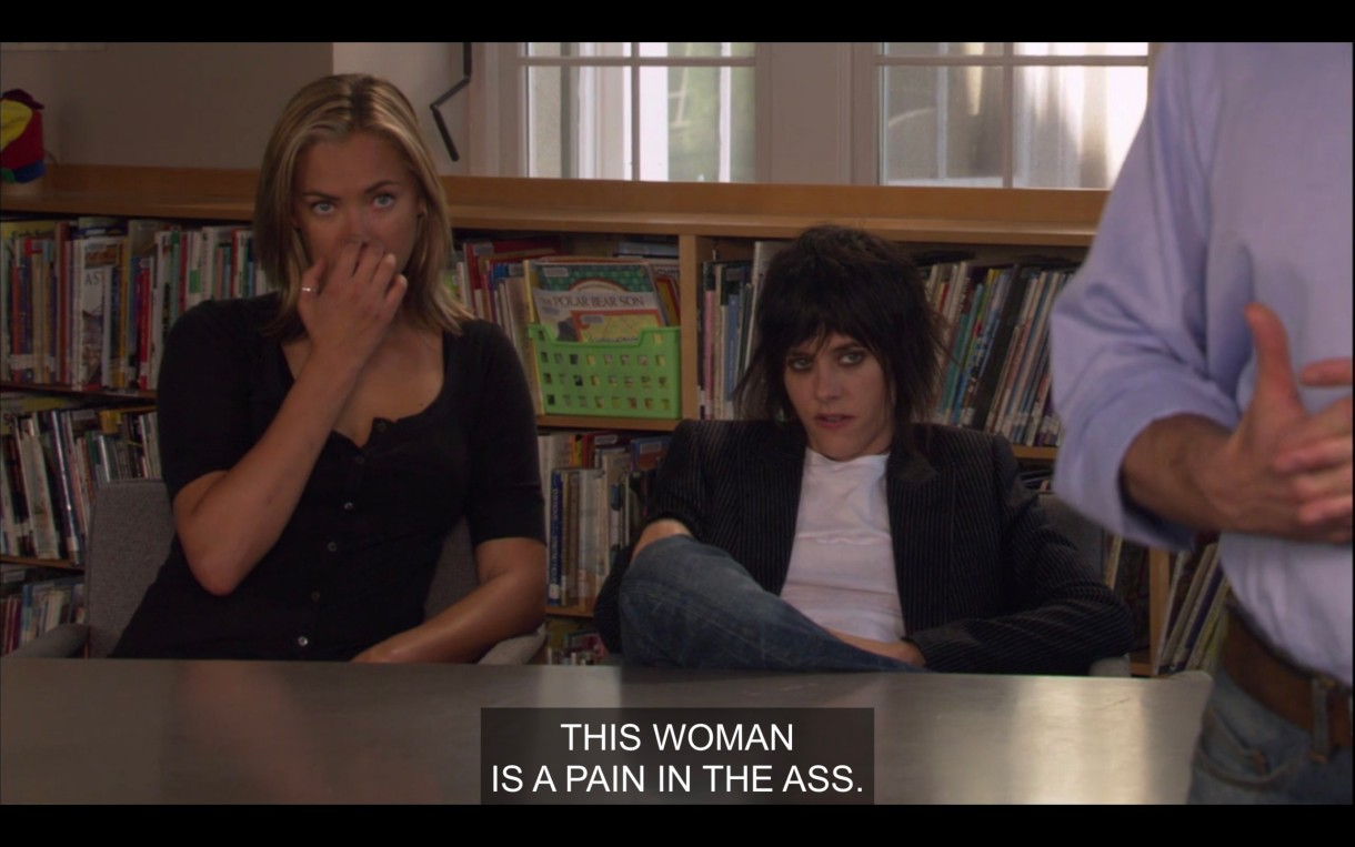 "Image Description: Paige and Shane sitting at a table in a school library. Shane's wearing a t-shirt and a blazer and slouching, Paige is sitting up straight with her hand over her mouth. The caption reads, ""This woman is a pain in the ass."""