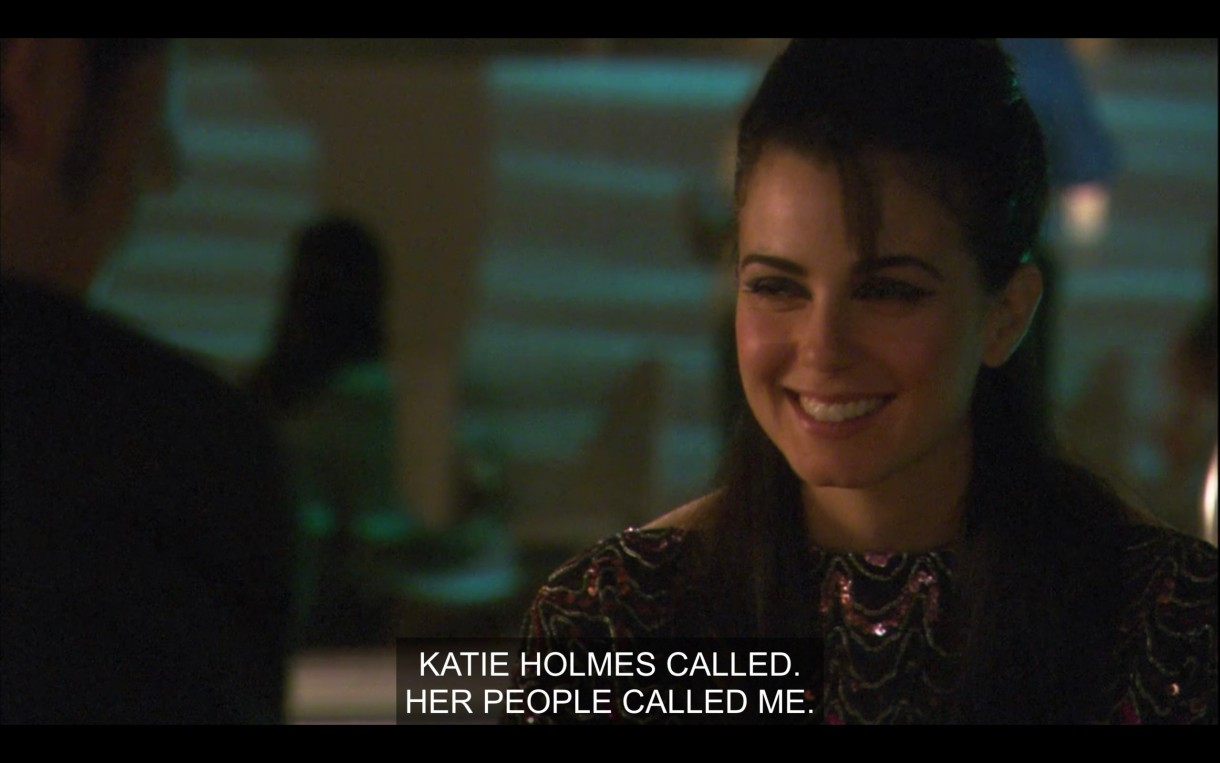 "Jenny smiling while somebody says ""Katie Holmes called. Her people called me."" It's an evening meeting near a pool, but you can really only see Jenny."