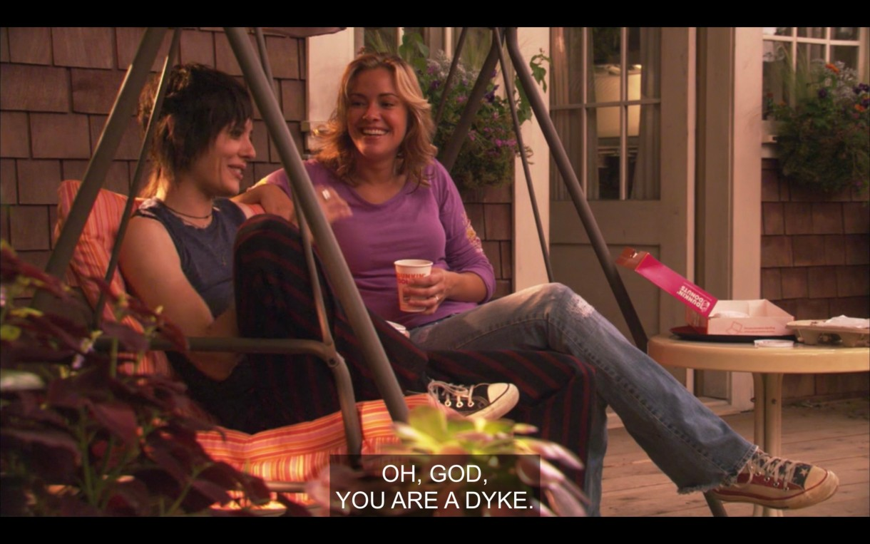 "Paige (wearing jeans and a purple top) and Shane (wearing dark pants and a blue tank top) sit next to each other on a porch swing. Shane says, ""Oh, God, you are a dyke."""