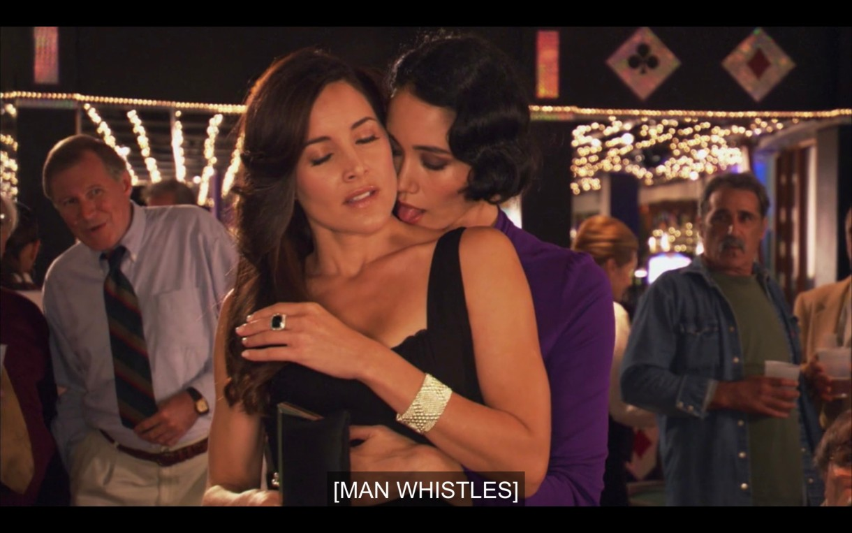 "A dark-haired person in a purple top hugging Helena (wearing a black dress) from behind, about to lick her neck. Subtitles read, ""[Man whistles]"""