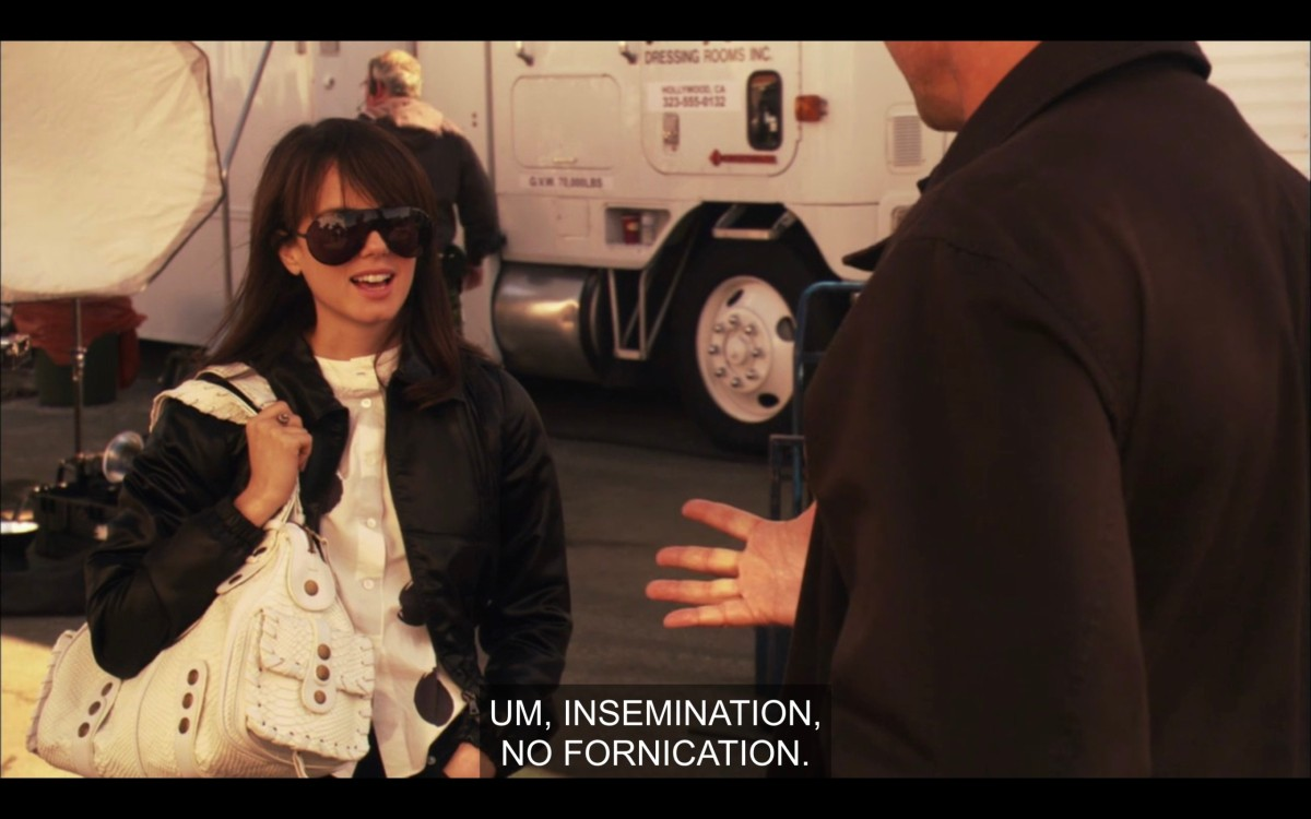 """Jenny on the Lez Girls film lot. She is wearing a white shirt under a black jacket, big black sunglasses, and a white leather purse on her right shoulder. She says, """"Um, insemination, no fornication."""""""