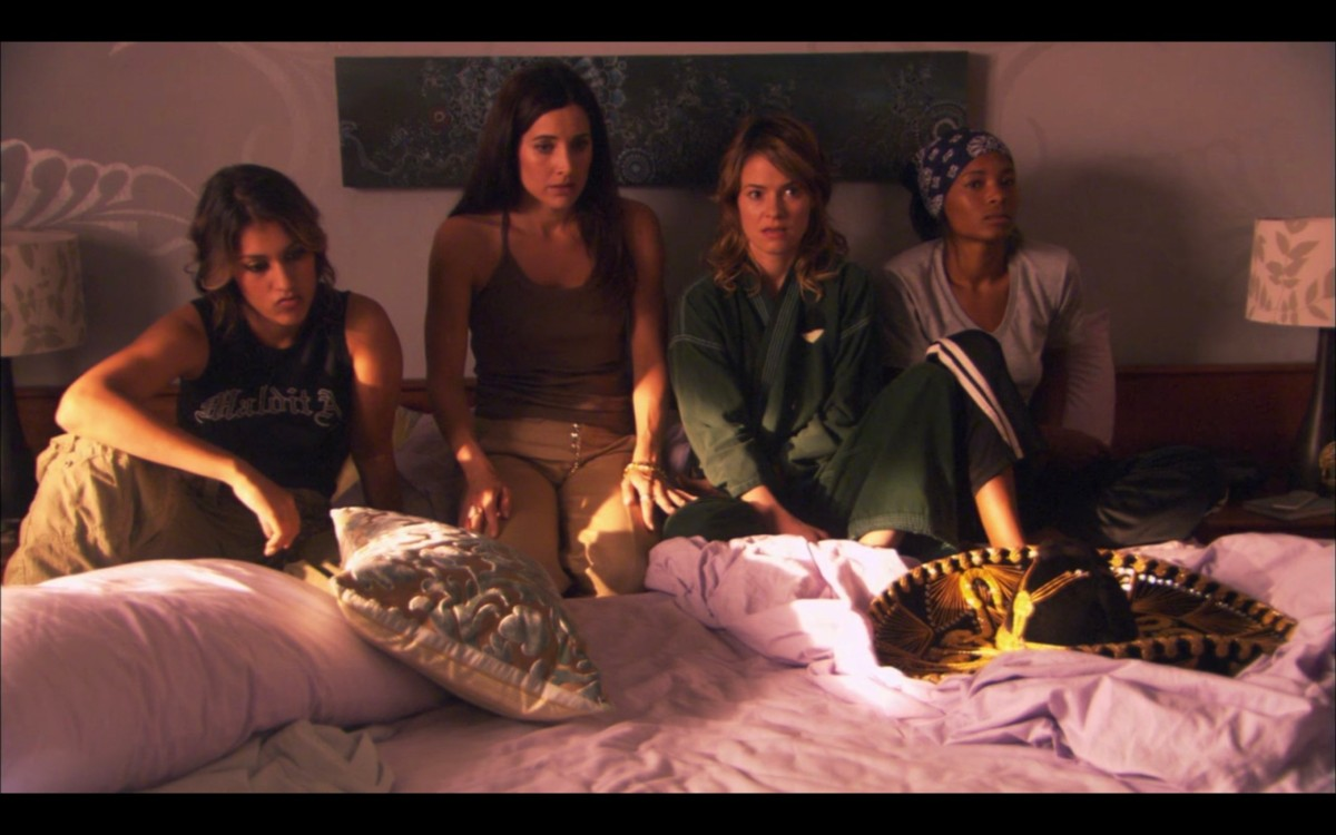 Papi, Helena, Alice, and Tasha sitting next to each other in Alice's bed on purple sheets. They all look surprised.