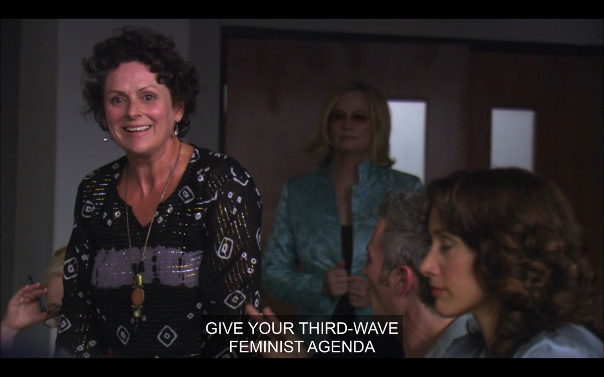 """A woman with short curly brown hair, wearing a black patterned blouse and a long necklace, says, """"Give your third-wave feminist agenda."""" Also in frame are Phyllis (in a teal jacket) and Bette."""