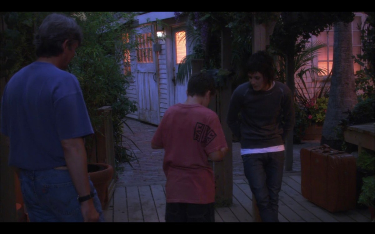 Shane, Shay, and their dad outside at dusk. Shane is leaning against a post. Shay and their dad's backs are to the camera.