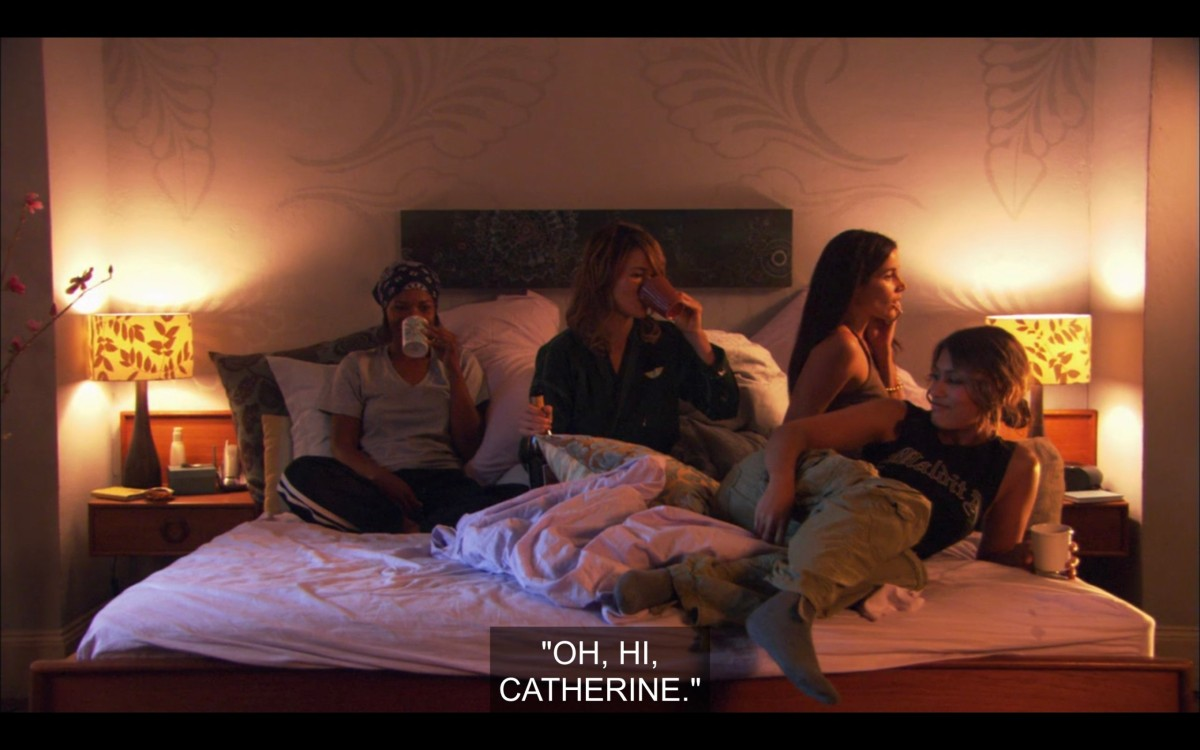 """Tasha, Alice, Helena, and Papi sitting in Alice's bed. Tasha and Alice are both drinking out of coffee cups. Helena is talking on the phone. She says, """"Oh, hi, Catherine."""""""