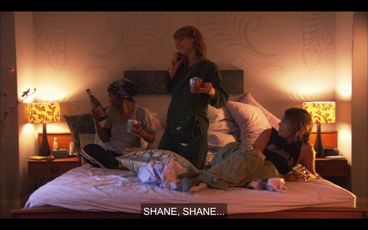 """Tasha, Alice, and Papi in Alice's bed. Tasha is holding a bottle of wine. Tasha and Alice are both holding coffee cups. Alice is talking on the phone. She says, """"Shane, Shane..."""""""