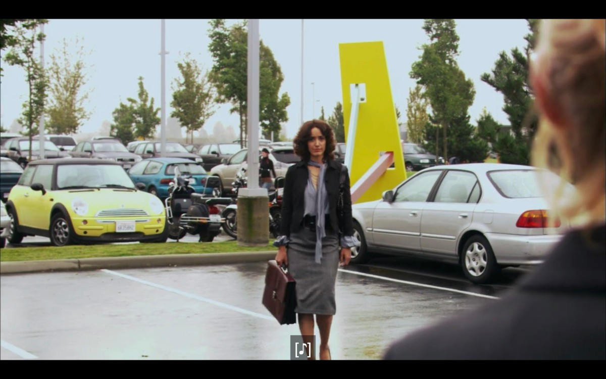Bette (in a grey skirt, black jacket, carrying a brown brief case) walking through a parking lot towards Tina (who is barely in frame).