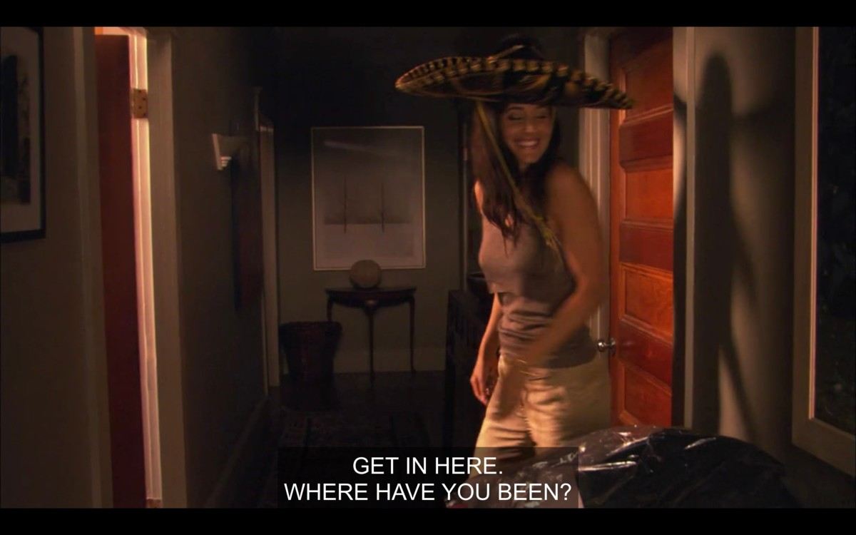 """Helena wearing a big sombrero hat in Alice's apartment. She says, """"Get in here. Where have you been?"""""""