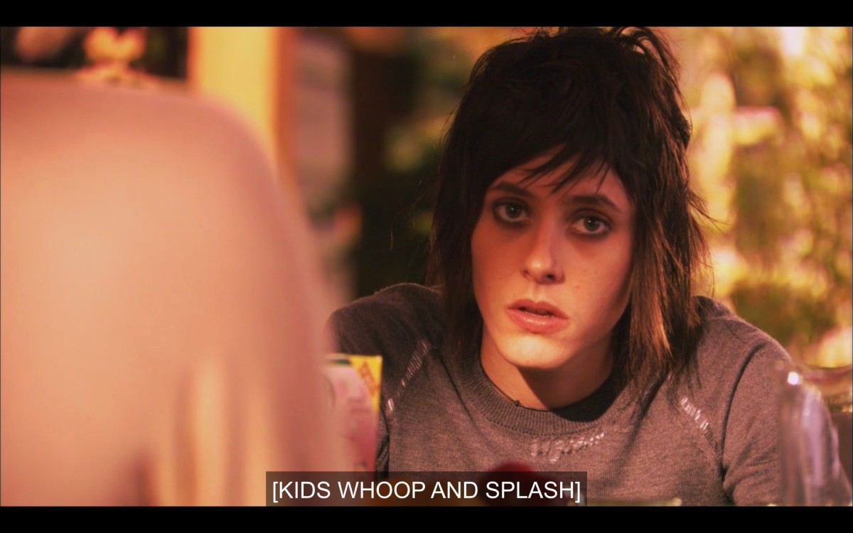 """Shane in a grey t-shirt, looking very tired, her black eyeliner smudged. Subtitles read, """"[Kids whoop and splash]"""""""