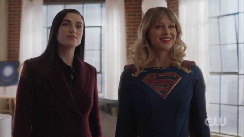 lena stands next to a supergirl smiling