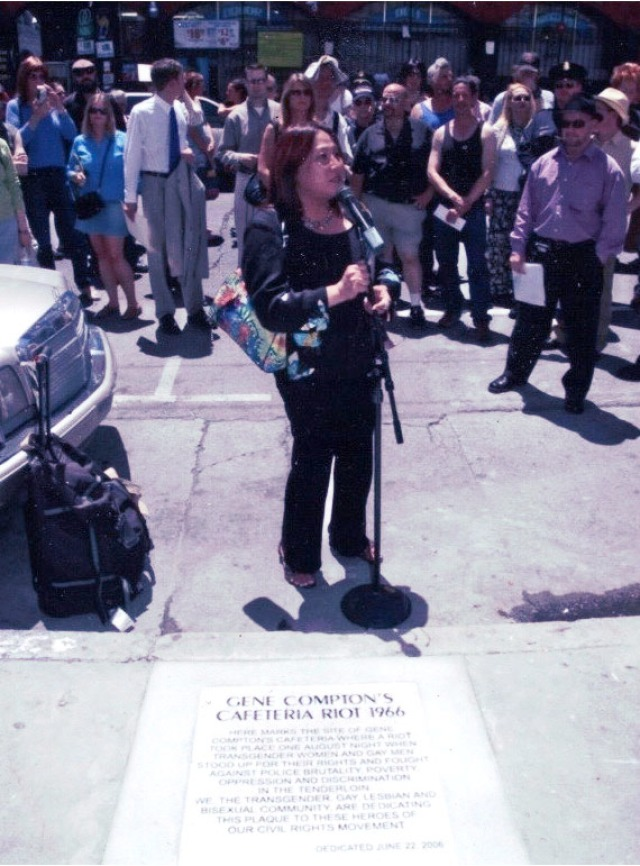 Cecilia organized and spoke at the 40th anniversary event for the Compton Cafeteria riots, which helped launch a national LGBTQ movement. Behind her stand a crowd of people.
