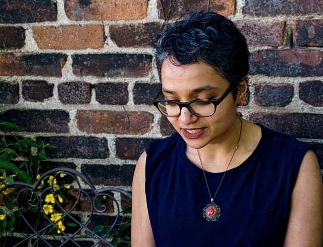 Himani sits on a wrought-iron bench against a brick wall, looking down.
