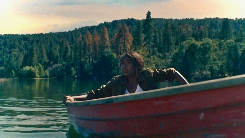 Image: A large lake surrounded by tall, vibrantly green trees. The character played by Janelle Monae is inside a red rowboat. She appears alarmed. She is wearing a white shirt and a green jacket, and clutching both sides of the boat, like she doesn't know where she is or how she got there.