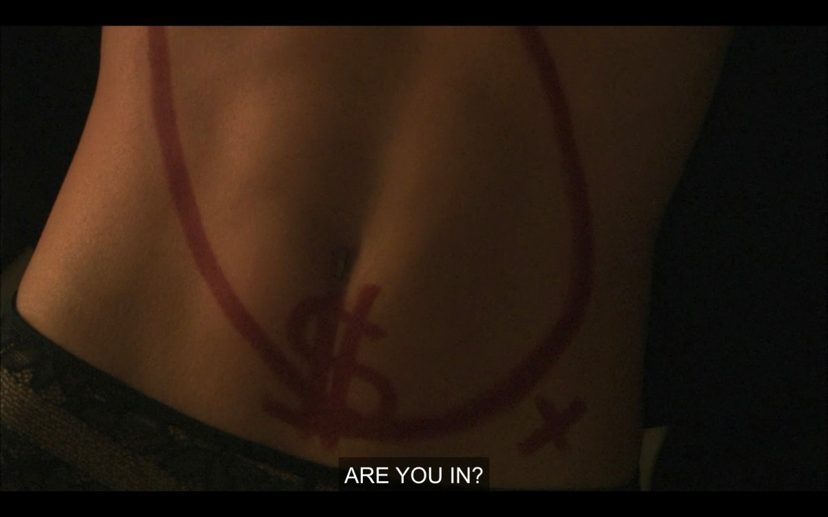 "A close-up shot of someone's stomach, with a red marker drawn circle, dollar sign, and x. ""Are you in?"""