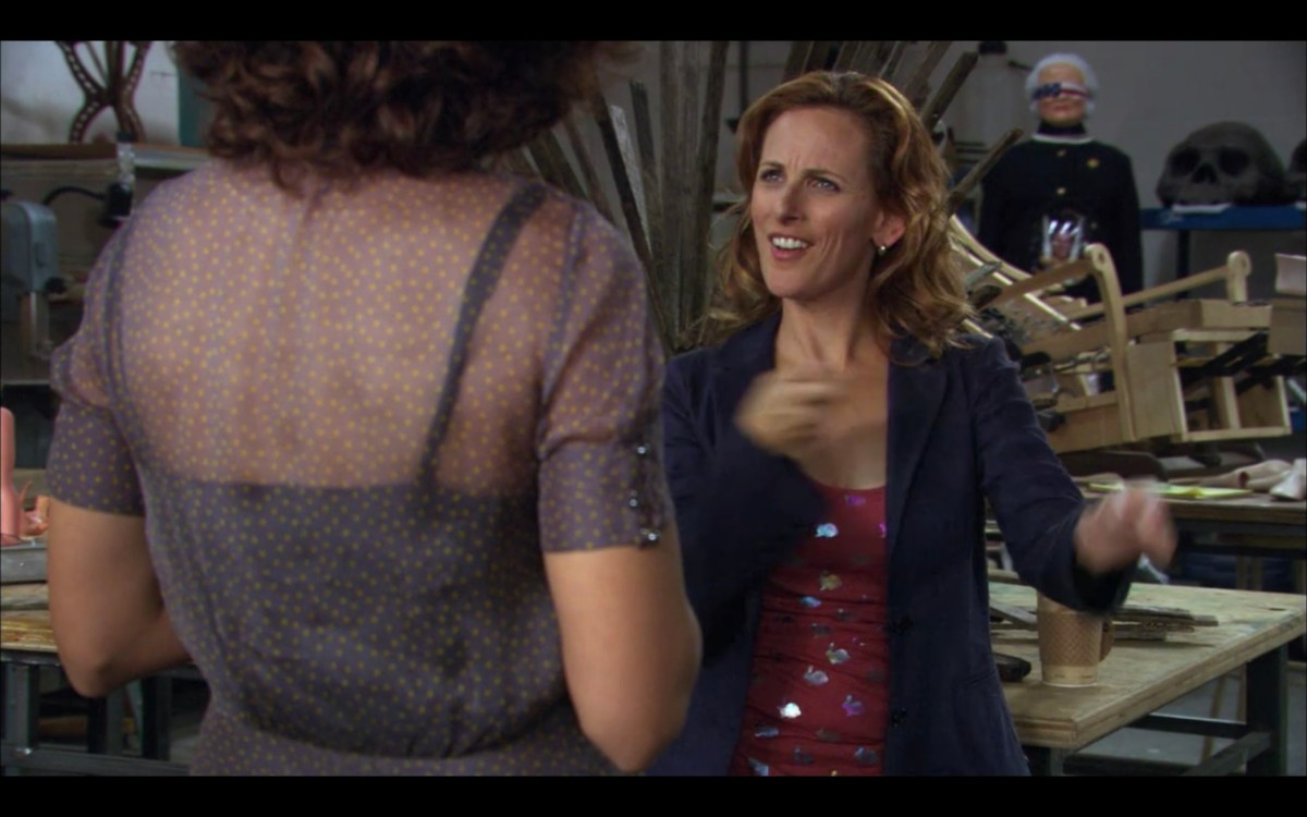 Bette (wearing a gray blouse, her back to the camera) is talking with Jodi (wearing a pink top under a blue cardigan) in Jodi's studio. Behind Jodi is her sculpture of Barbara Bush, who is blindfolded with an American flag.