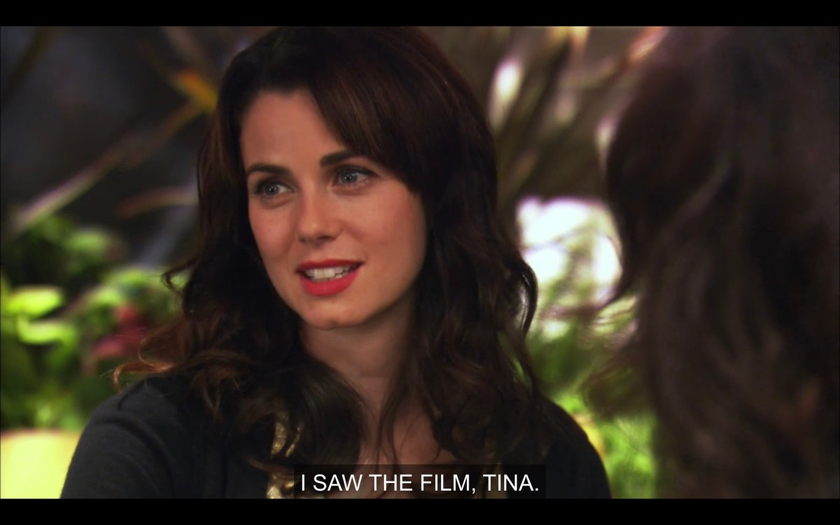 "Jenny is sitting outside, wearing red lipstick, her hair down and curled, and a black jacket .She says, ""I saw the film, Tina."""