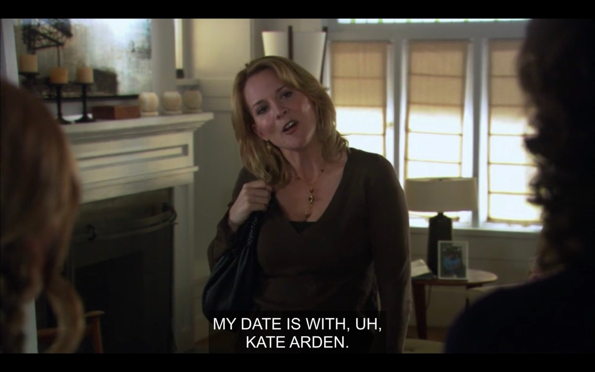 "Tina in her living room, wearing a brown top and a purse over her shoulder. Her head is tilted to her right, and is facing Jodi and Bette (who are off camera). Tina says, ""My date is with, uh, Kate Arden."""