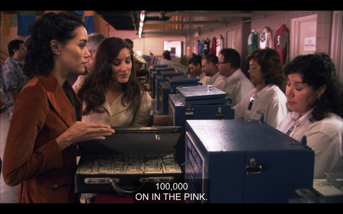 "Catherine and Helena at the horse races, about to hand over a briefcase full of cash over to the workers to place a bet. Catherine says, ""100,000 on in the pink."""