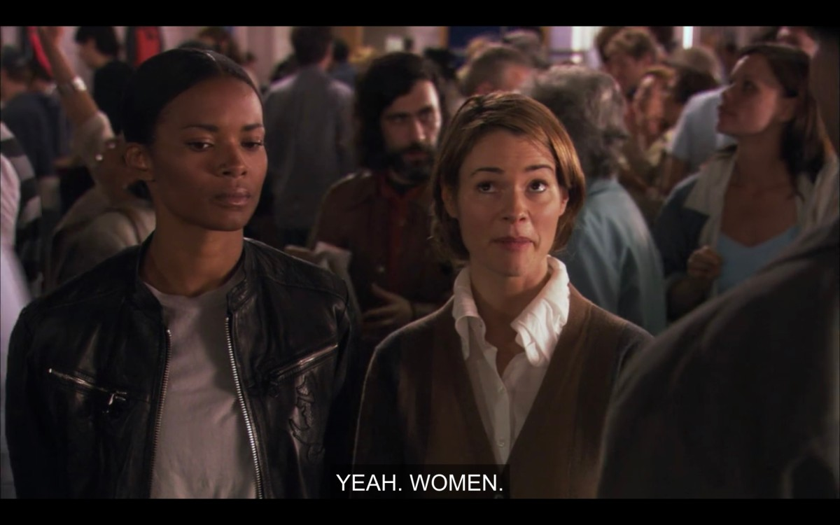 "Tasha (wearing a leather jacket) and Alice (wearing a white top and brown cardigan) stand in a crowd at the horse races.  Alice says, ""Yeah. Women."""