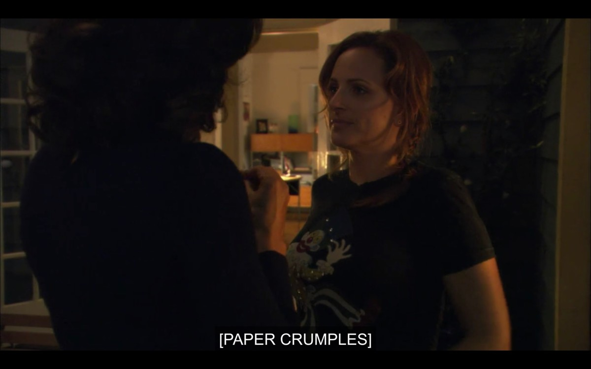 "Jodi and Bette (whose back is to the camera) in Bette's house. Subtitles read ""[Paper crumples]"""