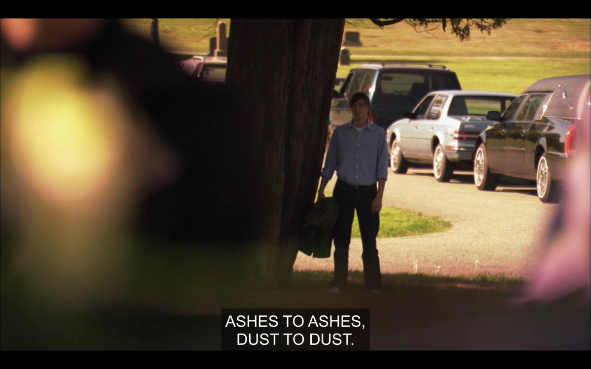 "Max (wearing a blue dress shirt) is walking along a dirt path. Subtitles read, ""Ashes to ashes, dust to dust."""